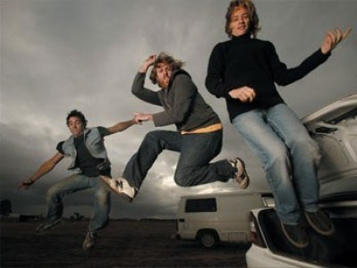 Spiderbait members jumping in the air in front of a tour bus.