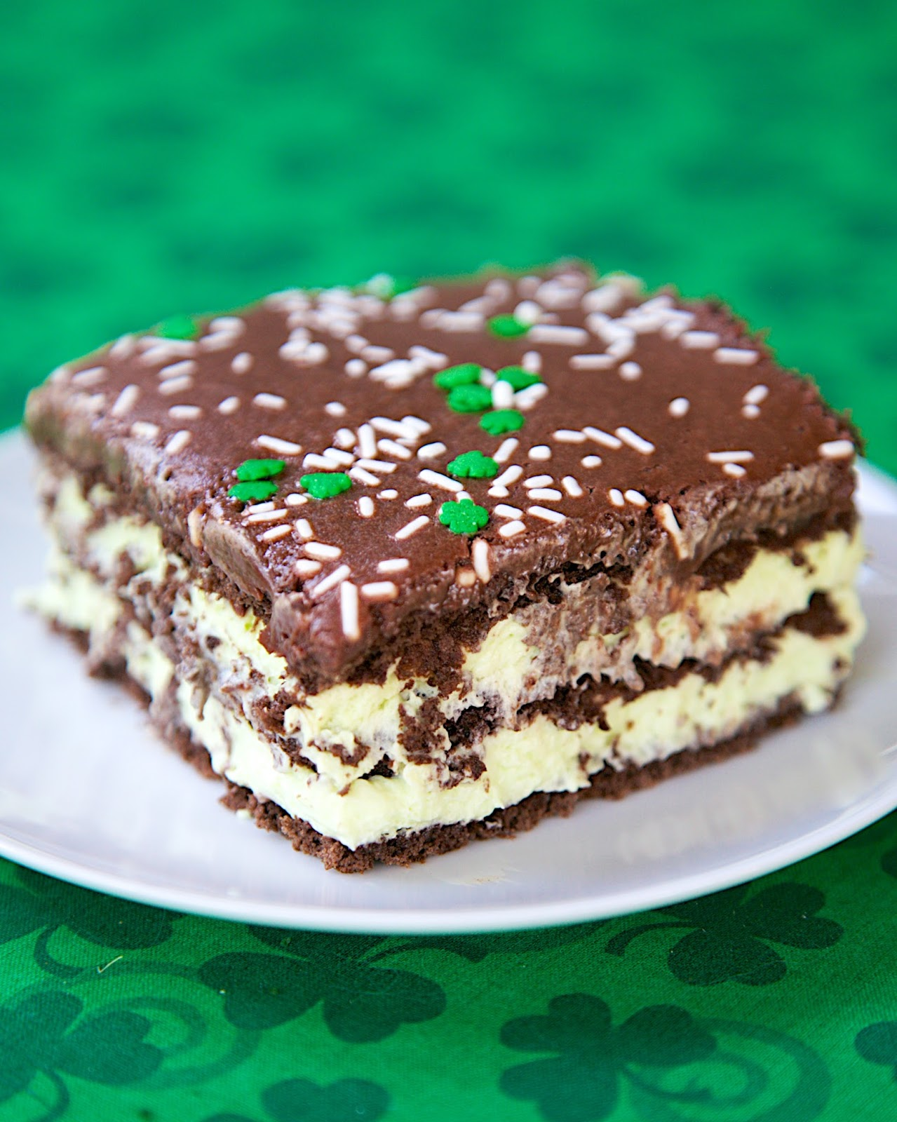 No-Bake Mint Chocolate Eclair Cake - chocolate graham crackers, pudding, cool whip, mint extract and chocolate frosting. Make ahead and refrigerate. Great dessert recipe for a crowd and St. Patrick's Day party!