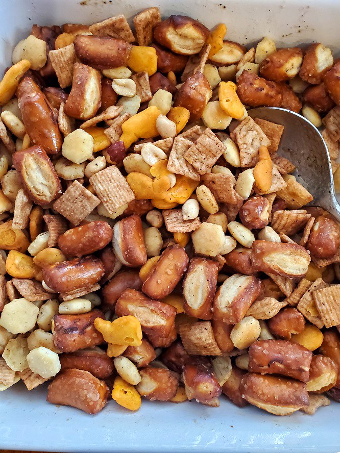 this is a full casserole dish of baked chex mix snack with pretzels, nuts and cereal along with cheese crackers