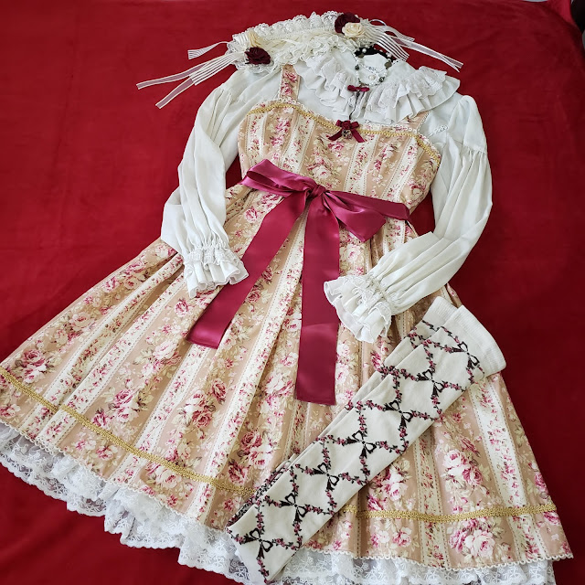 Third Coordinate, same dress with an ivory ruffle neck blouse, ivory rectangular headdress, and over the knee socks with flower and bow lattice print