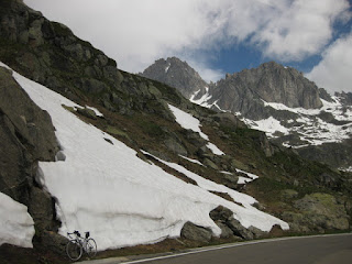 Bicycle parked against a snowbank near the summit of the Furkapass, eastern side, Switzerland