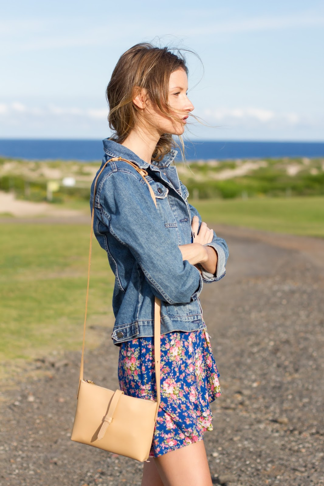fashion blogger and designer, Alison Hutchinson, is wearing a KAYVALYA blue floral wrap dress, Topshop denim jacket, and Witchery nude suede ankle boots