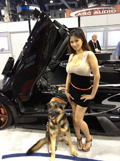 Tank posing with a model in front of a pretty car
