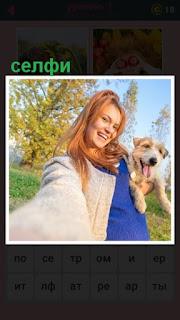 на поляне женщина с собакой в руках делает селфи