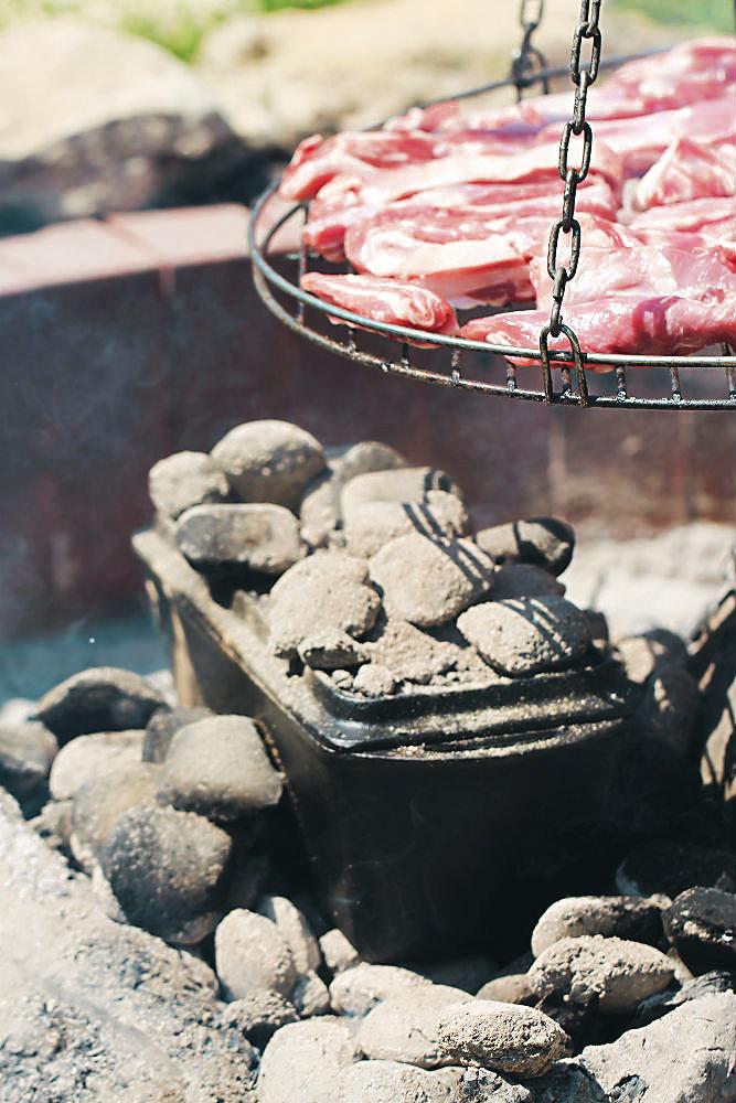 Der grüne Spargel in der Backform von Petromax/Dutch Oven in der Glut, den Deckel der Form mit Kohle bedeckt. Oben drüber garen die Lammrippchen auf dem Grill | Arthurs Tochter kocht von Astrid Paul. Der Blog für food, wine, travel & love