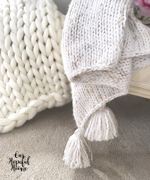 neutral colored chunky blanket and knit throw with tassels