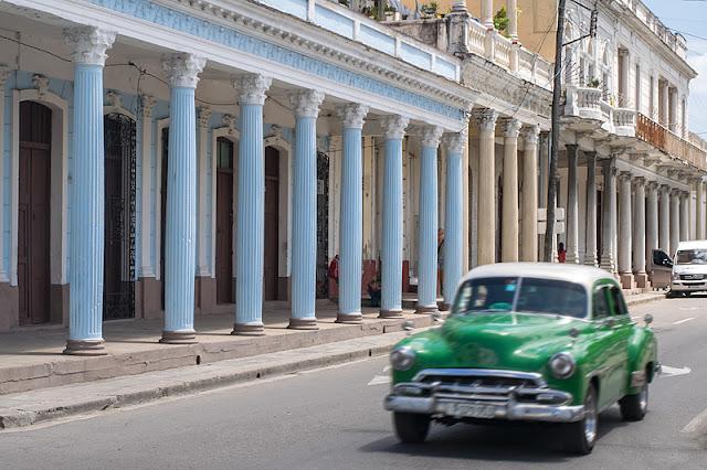 Une voiture file devant une colonnade sur le Paseo del Prado