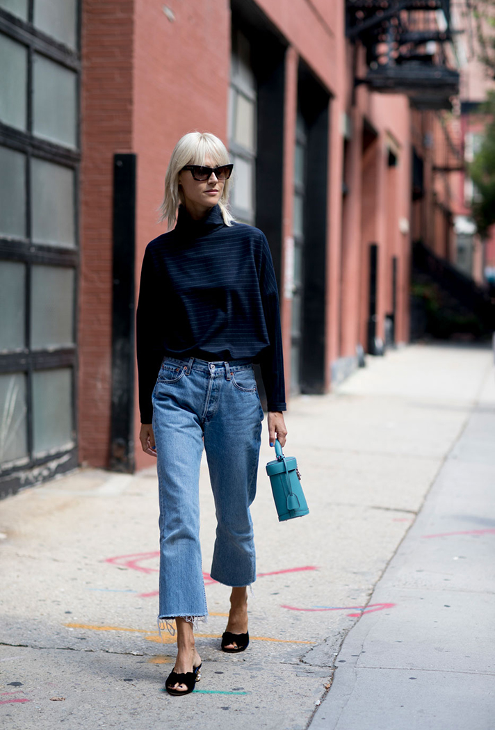 How to Wear Mule Sandals for Fall — Linda Tol Street Style Outfit With Cat-Eye Sunglasses, Raw-Hem Jeans, and Mini Bag
