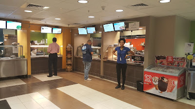 photo of cafe ordering area.  Employee smiling at camera.