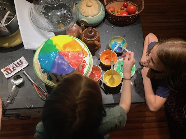 girls decorating a cake, view from above