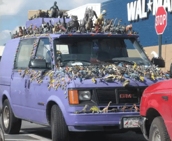 Purple van decorated with hundreds of toy dinosaurs in front of a Walmart, from Peopleofwalmart.com.