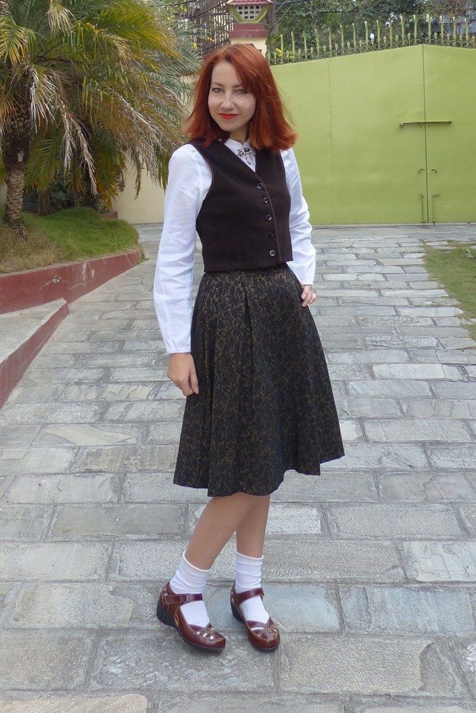 Schoolgirl inspired outfit: brown skirt, white blouse and waistcoat, flats with socks