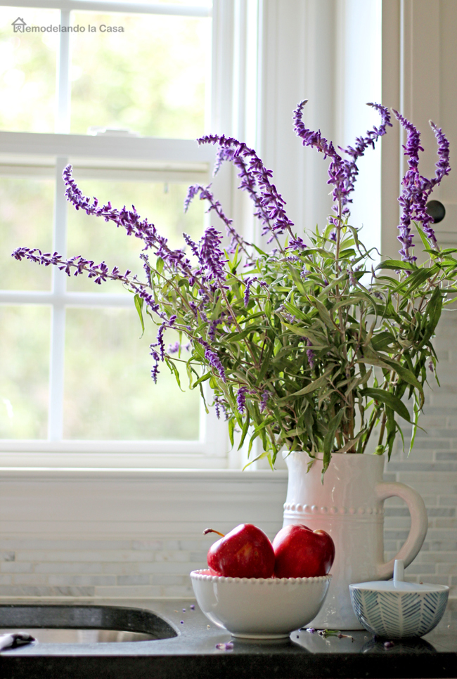 sage flower arrangement in white pitcher with a bowl of apples on the side of the kitchen sink with window