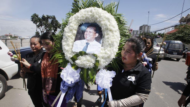 Cambodian community activists carry a wreath during the funeral procession of government critic Kem Ley in Phnom Penh, July 11, 2016.
