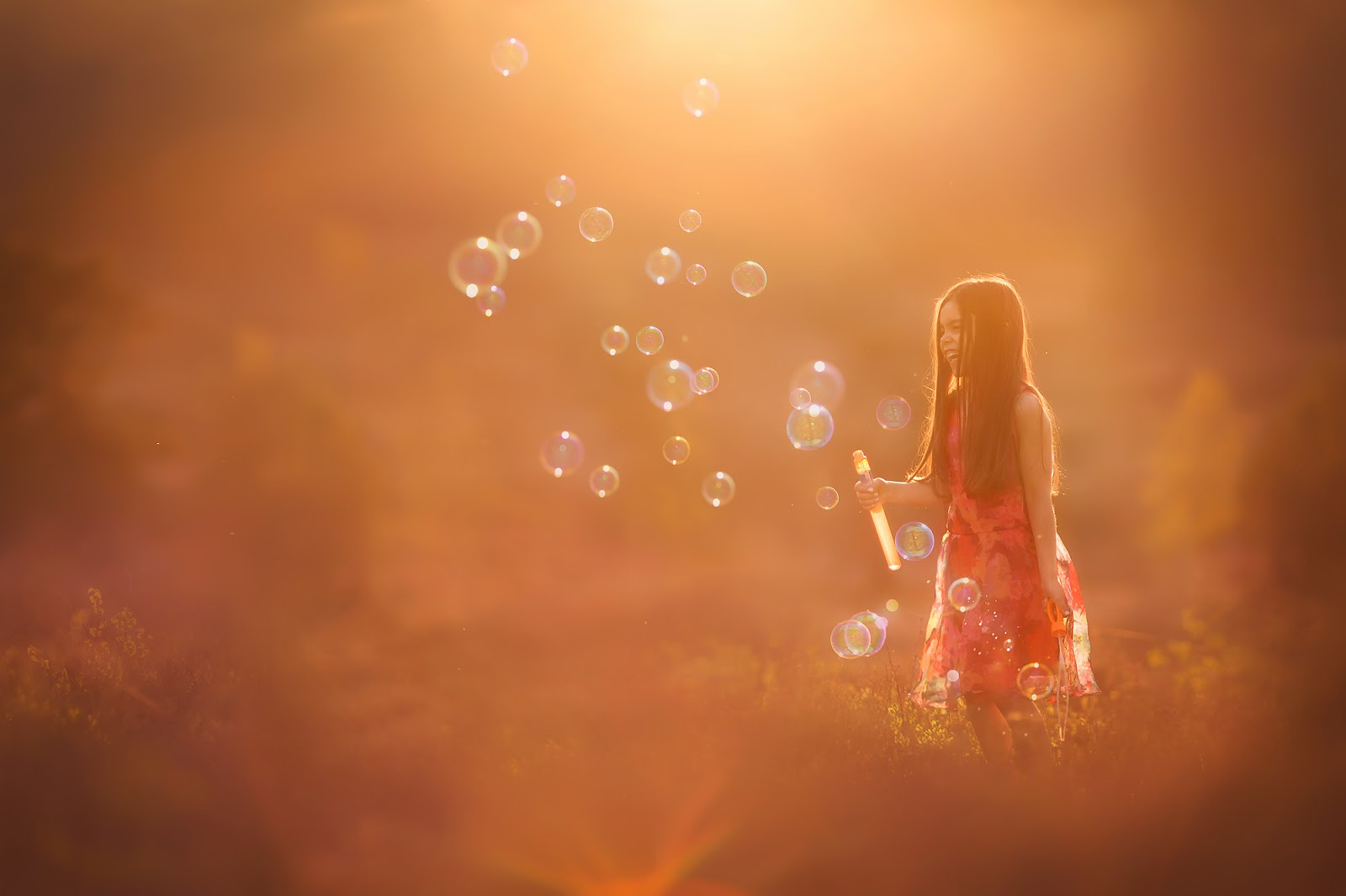 Canon color childhood portrait of a little girl having fun with a lot of bubbles in sunset by Willie Kers