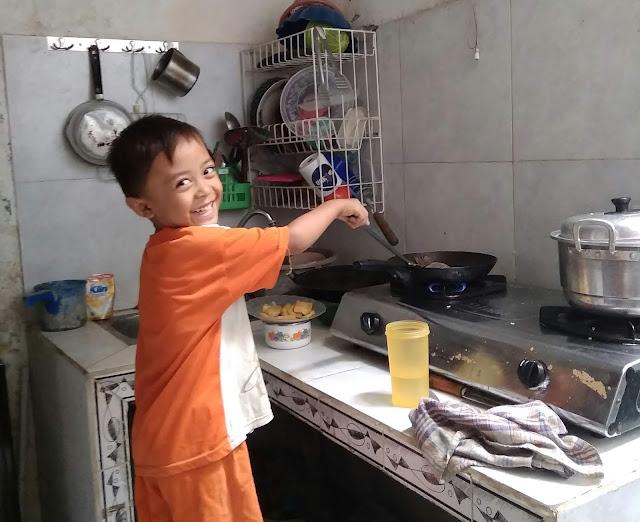 Mengajari anak membantu orang tua memasak di dapur