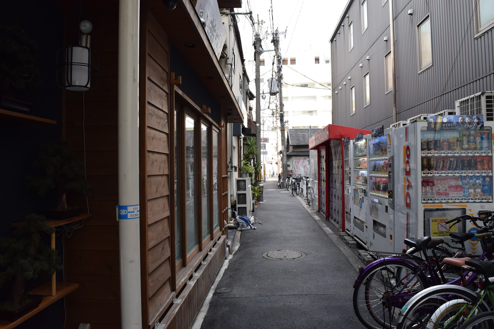 side street in Umeda, Osaka with vending machines and bicycles