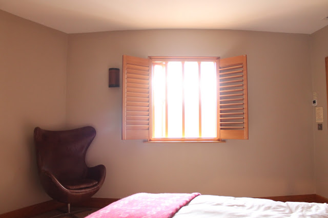 wooden shutters and brown leather chair in hotel room at the hardwick abergavenny