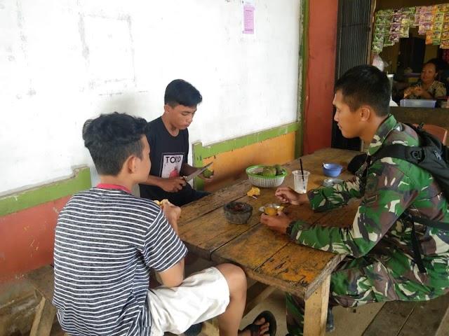 Anggota satgas TMMD jombs sambil makan mangga bersama pemuda desa