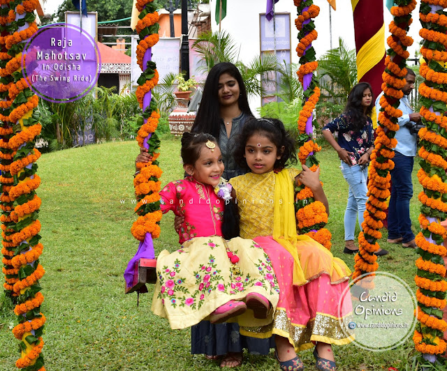 Girls enjoying a swing ride during Raja festival