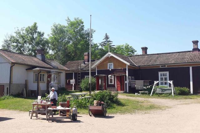 Vanhan talon pihapiiri. Taustalla kaksi rakennusta, edessä mies kahden pöydän ääressä.