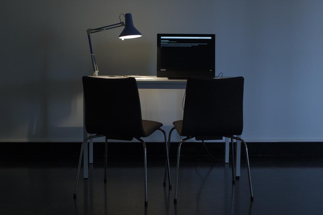 Photographie de l'installation dans laquelle le jeu a été présenté: un bureau, une lampe de bureau, un ordinateur et deux chaises.
