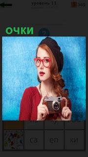 девушка фотограф в больших круглых очках с длинной косой и краской кофте