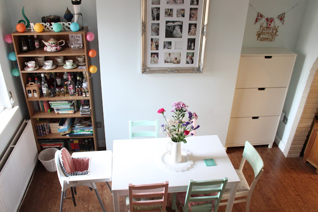 dining room with white pink and green table and chairs flowers and dark wooden floor