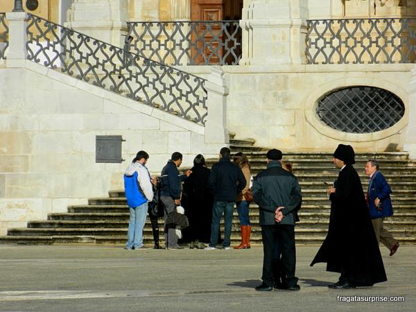 Estudante com a tradicional capa negra recebe os turistas no pátio da Universidade de Coimbra