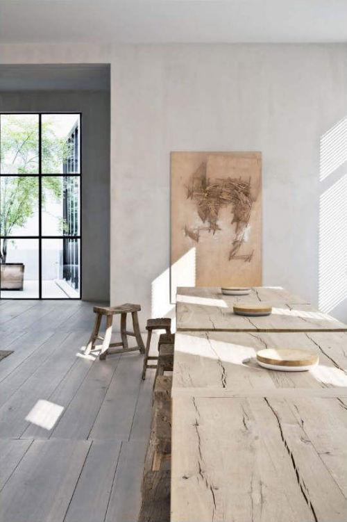 Leuchtend Grau: im großzügigem Wohnzimmer stehen zwei große Holztische mit Holzhockern