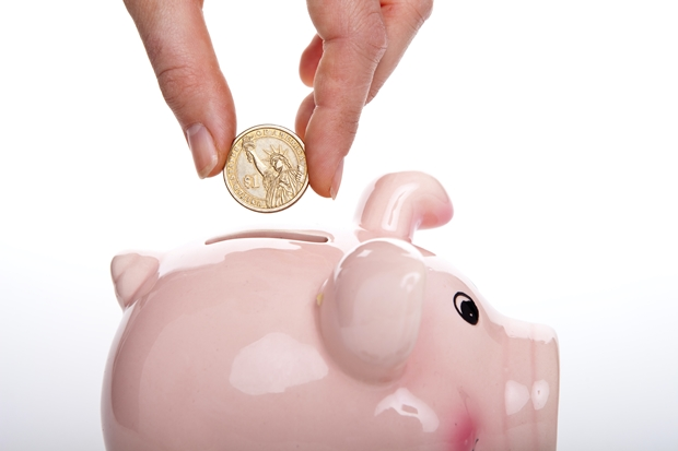 Mãos masculinas guardando uma moeda em um porquinho