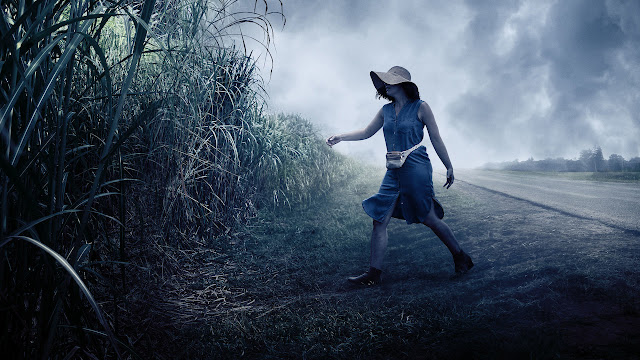 Woman wearing blue skirt a hat and a fanny bag trying to enter in the tall grass