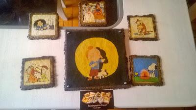 """Descrição da imagem: São sete quadrinhos que representam Tintim e Milú, Mafalda ouvindo rádio, Garfield e Odie, Calvin e Haroldo, Snoopy e Woodstock e o quadro """"Duas Fridas"""", de Frida Kahlo. Embaixo dos quadros, está o cartão da Recompondo Papel, que realizou o trabalho."""