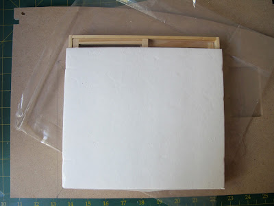 Pieces of a dollshouse building kit with a sliding door unit on top, covered with a piece of card, showing space at the top.