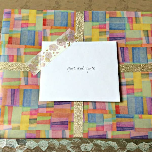 baby gift wrapped in watercolor rainbow wrapping paper
