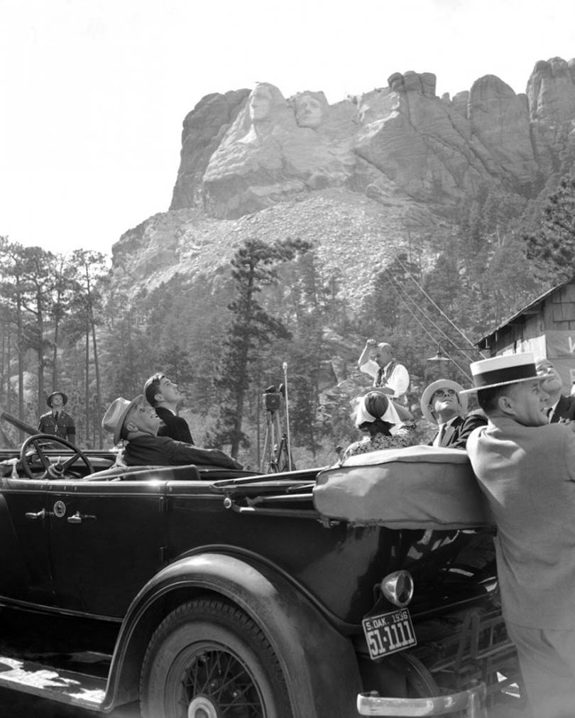 President Franklin Roosevelt visits Mount Rushmore, August 31, 1936. Sculptor Gutzon Borglum stands in the center with his hand raised, and the President, his son and other members of the delegation visiting the memorial.