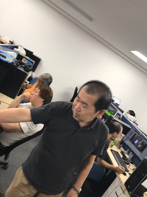 Yu Suzuki at the development studio, with the team hard at work