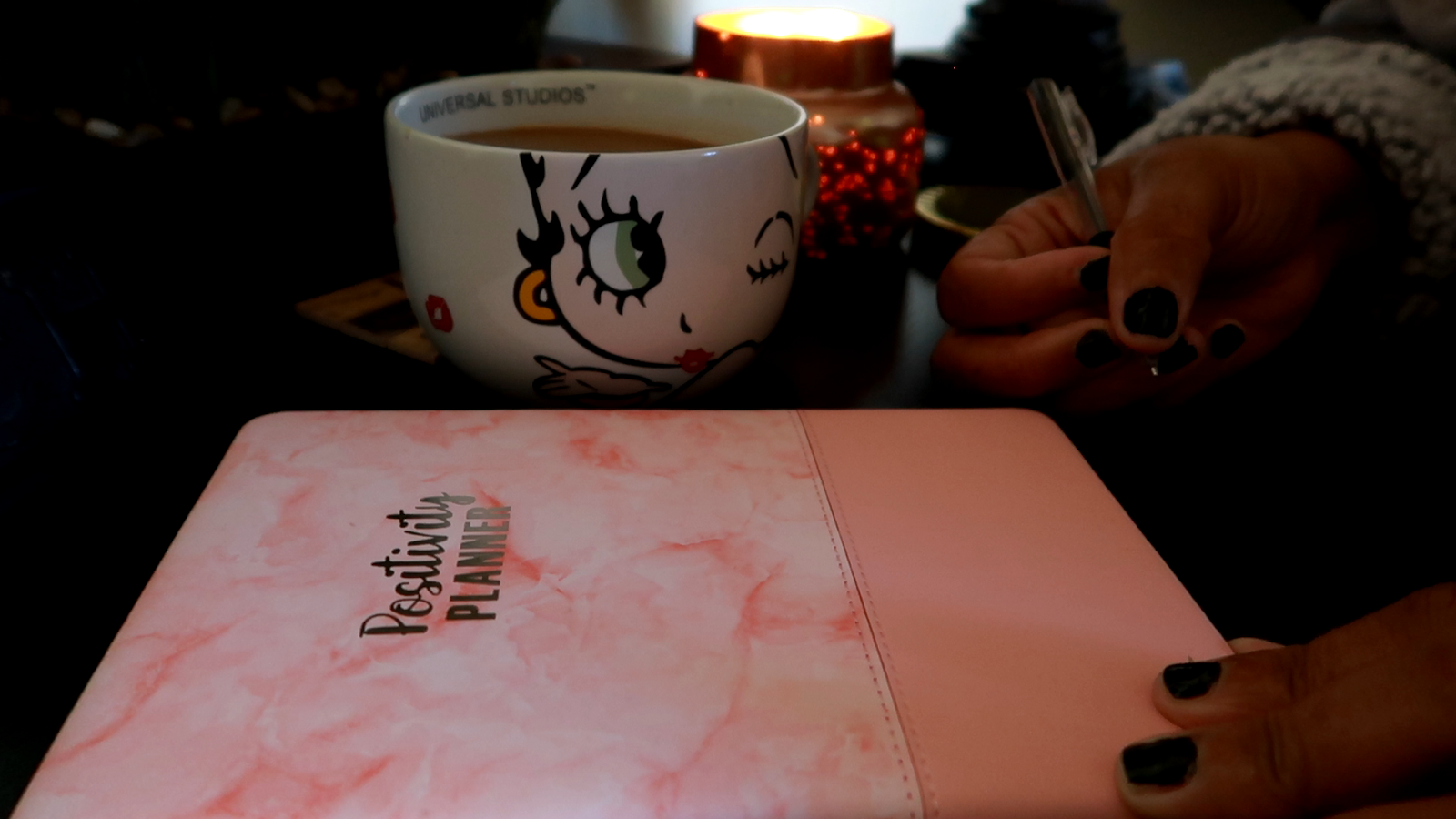 Image: Tangie Bell is writing in her journal. Drinking coffee out of her Betty Boop cup. Sharing on her blog her story about being in midlife crisis. Seen first on Bits and Babbles blog