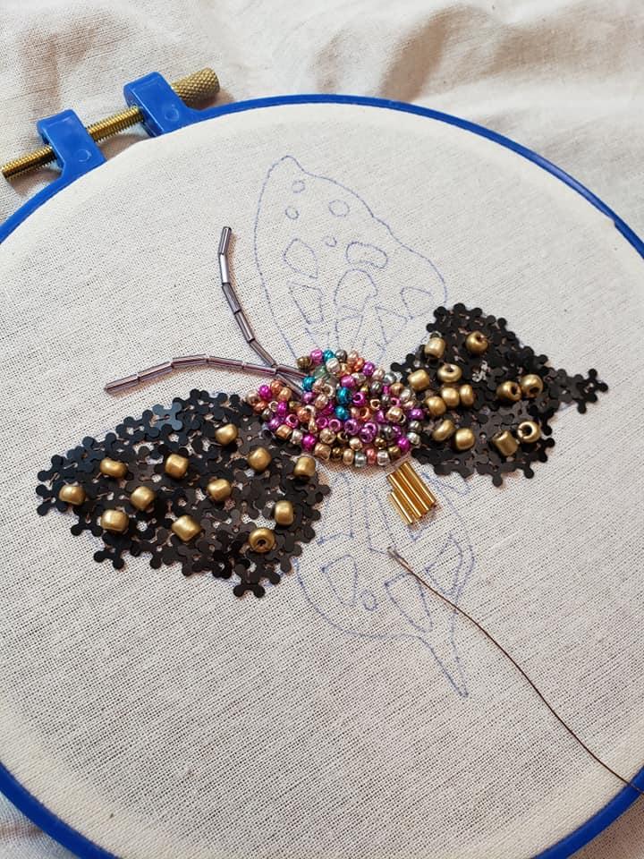 bastidor en proceso con bordado y pedrería en forma de mariposa