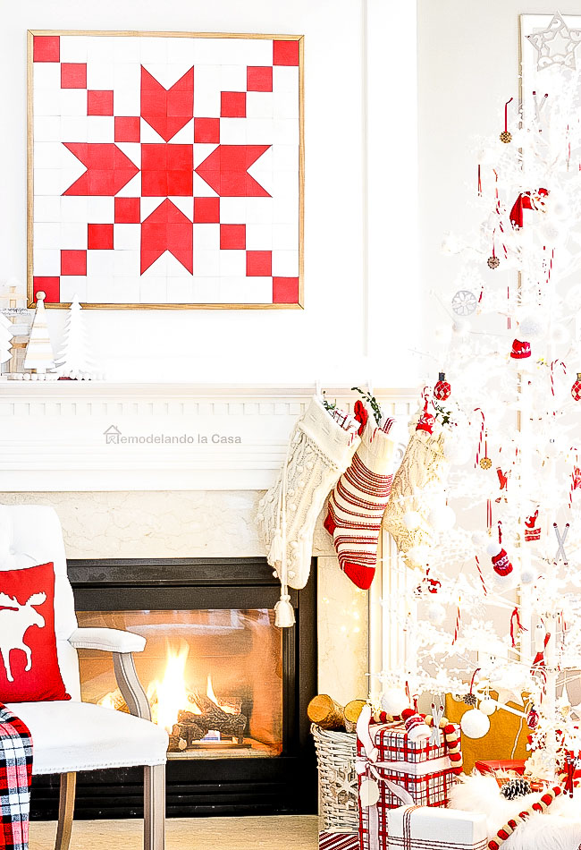 White and red Christmas mantel with white Christmas tree and a roaring fire