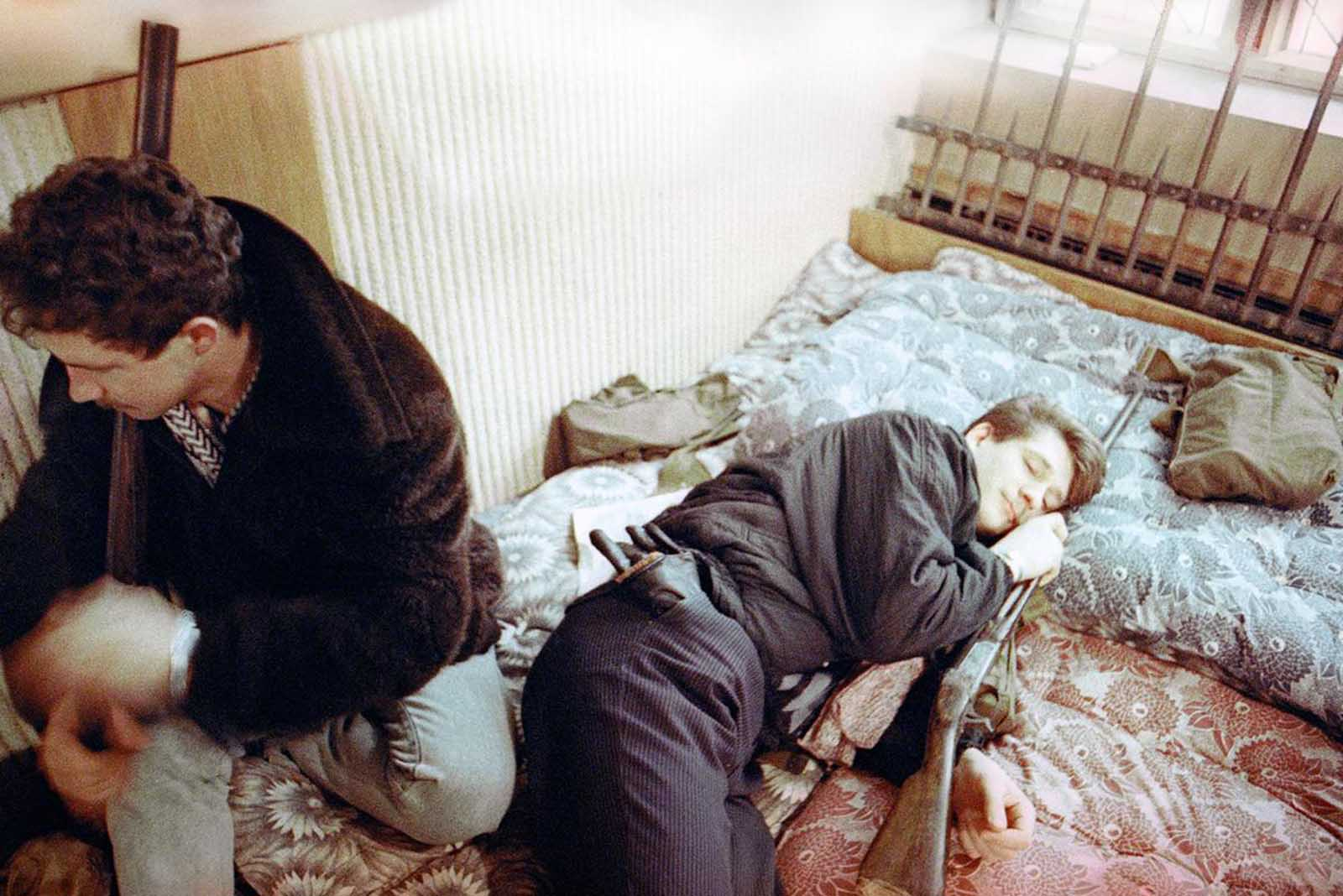 An armed Lithuanian volunteer guard wakes up as his fellow compatriot slept in Vilnius, Lithuania, on January 23, 1991. Hundreds of gunmen held vigil in the heavily fortified Lithuanian parliament while Soviet President Mikhail Gorbachev urged all Baltic republics to prevent further violence.