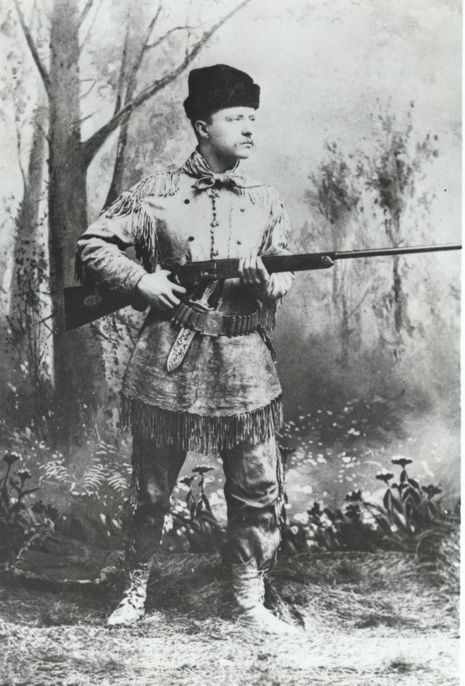 Theodore Roosevelt poses in a New York City photographer's studio wearing western-style clothing