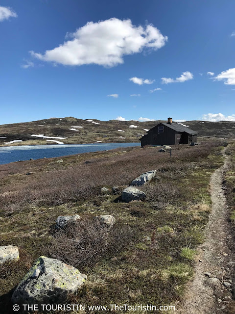 A trail along a lake that leads to a wooden cabin on the Hardangervidda Mountain Plateau in Norway.