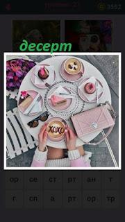 на круглом столе стоят десерт и чашка с кофе, лежит женская сумочка
