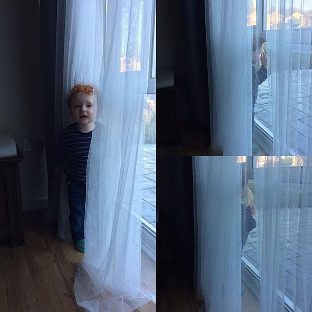 A redheaded child hiding in net curtains