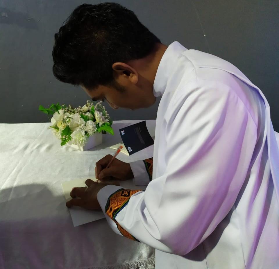 Diakon Saddam tengah menandatangani buku puisi Komuni atas ...