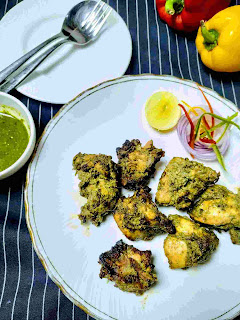 Serving hariyali kabab in a garnished plate green chutney, bell pepper and tablespoon in background