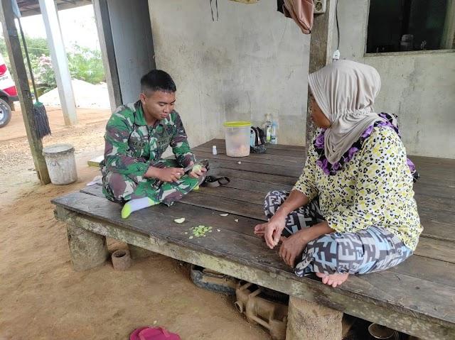 Anggota satgas TMMD bantu ibu asuh mengupas buah sekalian melaksanakan komsos