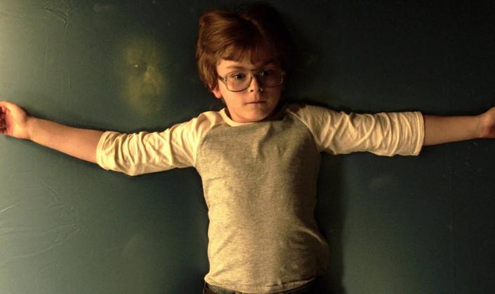 Imagem de capa: um personagem, interpretado pelo ator Julian Hilliard, um garotinho de uns dez anos, com cabelos castanho claros, um par de óculos e uma blusa branca com detalhes vermelhos que parece típica dos anos 80, deitado de braços abertos e olhando para cima num colchão verde-escuro, e sem saber, ao seu lado, um rosto demoníaco o observa, olhos amarelos, como se flutuasse no fundo de uma piscina.