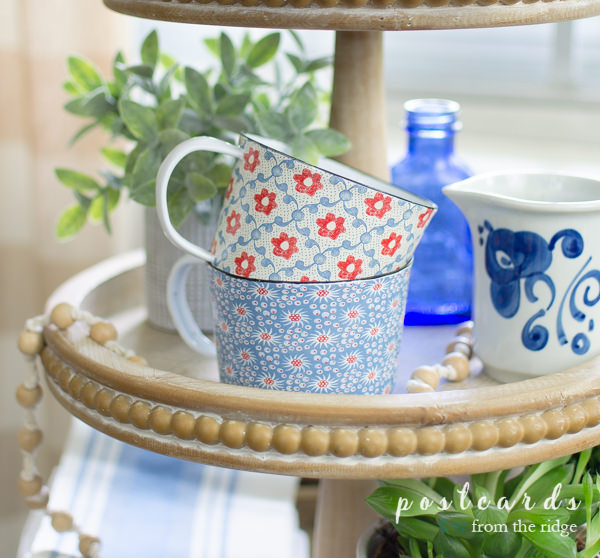 red and blue floral cottagecore enamel mugs in wood three tier tray